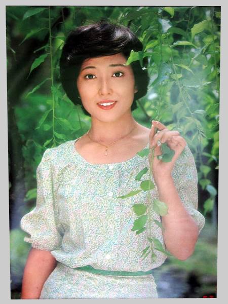 緑の葉を背景に、可憐なワンピース姿の若い頃の竹下景子
